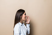 Side view of young woman in casual clothes looking aside, screaming with hands near mouth isolated on pastel beige background in studio. People sincere emotions, lifestyle concept.