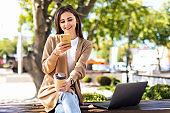 Beautiful young woman using laptop while sitting on a bench, holding mobile phone