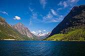 Picturesque scene of Urke village and Hjorundfjorden fjord, Norway. Drammatic sky and gloomy mountains. Landscape.