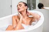 Attractive sexy woman lying in bath full of foam in modern bathroom. Beauty concept.