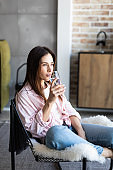 Young girl drinking water sitting on a couch at home and looking at camera