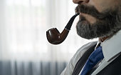 Portrait of vintage business gentleman, white man with mustache and beard, Caucasian person smoking pipe isolated in retro fashion design concept. Studio shot against dark background.