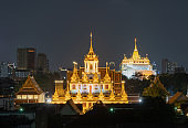 Loha Prasat Wat Ratchanatda and Golden Mountain pagoda, a buddhist temple or Wat Saket with skyscraper buildings in Bangkok Downtown, urban city at night, Thailand. Thai Landmark. Architecture.