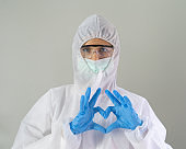 Portrait of western scientist or doctor woman with Covid-19 suit and mask working at hospital on grey background in medical health care and corona virus pandemic  concept.