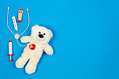 White teddy bear with toy stethoscope and toy medicine tools on a light blue background. Top view. Copy space for text