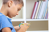 Kid cutting colored paper with scissors. Education, learning, paper craft, entertainment at home