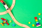 Baby kid toys background. Toy train, red airplane, wooden stacking pyramid tower and colorful blocks on light green background. Top view