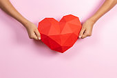 Hands holding red polygonal paper heart shape on light pink background