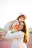 Mother hugs daughter at sunset in the lavender field.