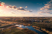 Aerial view of countryside and brook in evening at sunset light. Beautiful rural nature landscape