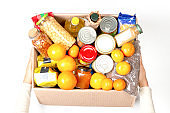 Hands holding food donations box with grocery products on white background. Top view