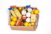 Food donations box with grocery products on white background. Top view