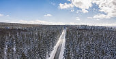 Aerial view of cars driving by the road through the forest covered by snow in winter and cloudy sky, including Copy space