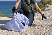 Volunteer hand with protective glove cleaning beach from plastic. Woman picking up plastic bottle trash and putting into plastic bag for recycle