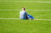 Sad alone boy with backpack sitting stadium outdoors
