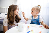 Mother and Daughter paint together. The child draws with his mother.