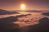 Autumn in the mountains. View of the peaks of mountains and foggy valley during sunset. Beautiful nature landscape. Carpathian mountains. Zakarpattia Oblast, Ukraine