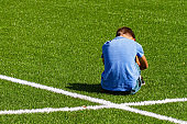 Sad disappointed boy sitting on the grass in stadium
