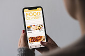 Food delivery app on a mobile phone. Restaurant order online. Woman using smartphone to get take away lunch home delivered. Fast courier service. Suhsi and Pizza menu mock up in cellphone screen.