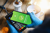 contactless payment on a mobile phone. Close up of a woman hand paying contactless with a smartphone screen application. Hand holding smart device to pay. Mockup cellphone screen.