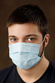 Natural portrait  Young man with medical face mask. Wearing surgical mask  to prevent infection, airborne respiratory illness. Coronavirus protection.