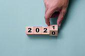 Hand flipping wooden cubes block for change 2020 to 2021.  Happy new year to start new project and business concept.