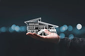 Business holding virtual infographic house on hand. Real estate investment concept.