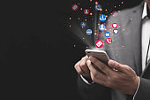 Social media and marketing concept, Businessman holding white smartphone and using colourful social media icons.
