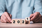 Businessman flipping wooden cubes block to change 2020 to 2021 year on wooden table. Happy new year and start new business concept.