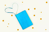 Blue diary and golden rounds. On a light background. Heart-shaped bookmarks.