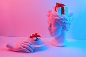 Composition with gypsum bust and hand. A box with a red ribbon in head and on the podium. Gift concept