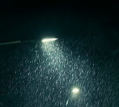 Raindrops illuminated in streetlight at night