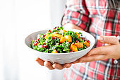 Vegetable salad bowl in woman hands. Fresh kale and baked pumpkin salad. Healthy eating concept