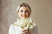 Beautiful bride with a calla lilies bouquet in a bright hotel room.