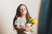 Adorable smiling little girl with yellow tulips.
