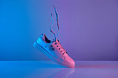 Trendy white teenage sneakers with flying laces in trendy neon light. New shoe in retro surreal red, blue gradient light
