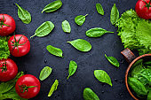 Fresh grape tomatoes with salad and spinach Leaves on black stone background. Vegan veggies diet food.