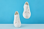 Pair of fashion stylish white sneakers, Running sports shoes on pastel blue background.