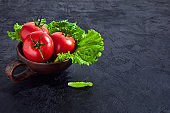Fresh grape tomatoes with salad Leaves on black stone background. Vegan veggies diet food. Herb, red tomatoes, cooking concept.