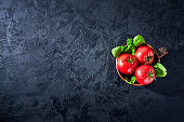 Fresh grape tomatoes with spinach Leaves on black stone background. Vegan veggies diet food. Herb, red tomatoes, cooking concept.