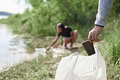 Hand picking up paper cup cleaning on the river beach. Volunteer cleaning up the garbage. Stop plastic. Recycling.