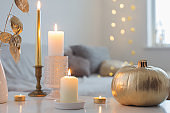 home decor with golden pumpkin and burning candles
