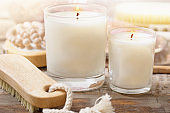 aromatic candles with massagebrush on wooden background close up