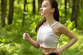 Fitness sport concept. Slender girl runs on a background of trees