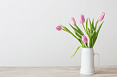 pink tulips in white ceramic jug on wooden table on background white wall