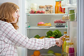 teenager girl at fridge with food