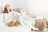 teenager girl with teddy bear  on sofa at home