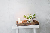 lily of the valley in vase with burning candles on background old white wall