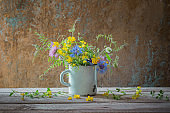 summer flowers in old cup on wooden background