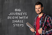 """Young man and text ,, Big journeys begin with small steps """""""